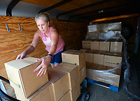 Erlyn Payne of Huntsville, unloads a trailer filled with 200 boxes of food Thursday, July 29, 2021, from the Northwest Arkansas Food Bank as she prepares for the eighth annual Parent Up event organized by Altrusa International of Washington County. The event, which is planned for 11 a.m. to 1 p.m. Saturday at Prairie Grove Elementary School, provides school supplies, food, books, backpacks and personal care items to about 300 families in the Prairie Grove, Farmington, Lincoln, West Fork and Greenland school districts. Sponsors of the event include Harps, Altrusa International Foundation, Centennial Bank, Ozarks Electric/Ozarks GO, Collier Drug Stores, United Bank, Arvest Bank, Beavers and Broomfield Dentists, Delta Dental, Storms Orthodontics, Jack Links and dental hygienist Kendra Colby. Visit nwaonline.com/210730Daily/ for today's photo gallery.<br /> (NWA Democrat-Gazette/Andy Shupe)