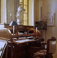 An English roll-top desk dominates one wall of the atelier living room, situated between a pair of tall, shuttered windows overlooking the cobbled street