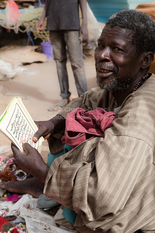 Senegal, Touba.  Street Vendor Reading a Booklet in Arabic.