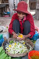 Cambodia.  Market near Siem Reap.  Woman Cutting Papaya for Salad Mixture.