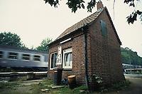 GERMANY, old brick barrier station house / DEUTSCHLAND, altes Bahnwaerter Haus und vorbeifahrender Zug
