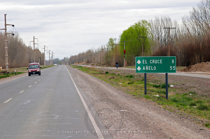Long straight road through the landscape towards the region town Anelo, a roadsign with Anelo and El Cruce Neuquen, Patagonia, Argentina, South America