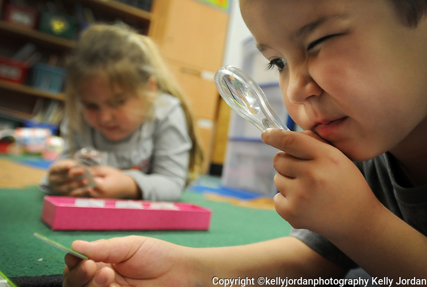 """Kelly.Jordan@jacksonville.com--111011--Dylen Ford, 5, uses a magnifying glass to sort photographs of the seasons and match them with the time of year they fall during science time in his kindergarten class at John A. Crookshank Elementary School in St. Augustine Thursday November 10, 2011. Teachers like his kindergarten teacher Shea Grammer are spending more of their own money to pay for classroom supplies. Grammer was one of the lucky ones because she is among 54 Jacksonville area teachers who has received donations totaling more than $30,000 to fund 68 classroom projects through Donors Choose, a non-profit organization that connects donors with public school teachers who need classroom materials. Grammer got money for a hands-on science learning project entitled """"Exploring Science"""" which fits with her goal to """"make science fun.""""(The Florida Times-Union, Kelly Jordan)"""