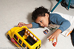 Education preschool 3-4 year olds boy playing on floor with toy bus and human figures talking to himself