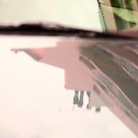 The reflected images of two different modern buildings on the windscreen and the hood of a parked car, divided by the windscreen wiper, under a cloudy sky. This is an enlargement of the original photo (Paris, 2011).<br /> <br /> Le immagini riflesse di due diversi edifici moderni sul parabrezza e sul cofano di un automobile parcheggiata, divise dal tergicristalli, sotto un cielo nuvoloso. Questo è un ingrandimento della foto originale (Parigi, 2011).