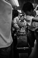 Train attendants move through a crowded passenger car to sell food and toys to passengers in China.