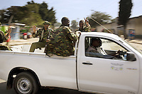 Kenya. Rift Valley province. Nakuru. 25.01.2008. Kikuyus policemen drive on a pick-up truck. The men carry weapons in order to defend themselves and prevent the violences occuring during the inter-ethnic strifes. They wave with their hands and make a victory sign with the fingers. The Kikuyus are Kenya's most populous ethnic group. © 2008 Didier Ruef