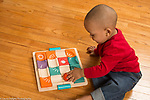 18 month old toddler boy playing with ball and ramp maze toy