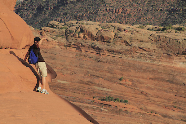 Young man peering over the edge in Arches National Park, Moab, Utah, USA. .  John offers private photo tours in Arches National Park and throughout Utah and Colorado. Year-round.