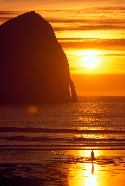 A single figure watches the sun ball setting in the orange sky and ocean at Cape Kiwanda, Oregon coast.