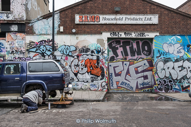 Car mechanic working in the street in Hackney Wick, an area undergoing rapid gentrificarion.