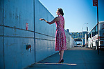 Woman reaching out to light coming through wall