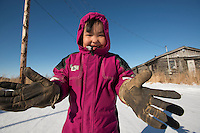 """Danny-Girl"" from Zackar Levi School in Lower Kalskag puts on her gloves to go skiiing with her Skiku coaches. Skiku is a non-profit organization with the mission of creating a sustainable Nordic ski program in communities throughout Alaska. Volunteer coaches travel to villages each spring to instruct youngsters and distribute donated equipment with the goal of establishing ski programs at rural schools.  Photo by James R. Evans"