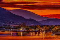 Fine Art Print of a fiery sunrise over Penticton as lake Okanagan picked up the red glow from the sky as the sun was just beginning to over the mountains.