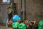 """© Joel Goodman - 07973 332324 . Manchester , UK . 05/04/2015 . A couple embrace alongside bagged rubbish, in Manchester's """" Gay Village """" . Revellers on a Saturday night out during the Easter Bank Holiday weekend . Photo credit : Joel Goodman"""
