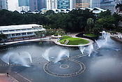 A young boy stretches to touch the water fountains of KLCC park in Kuala Lumpur, Malaysia.