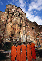 Monks praying to Buddha Image House Lankatilaka Temple Polonnaruwa Sri Lanka.