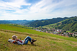 Germany, Baden-Wurttemberg, Black Forest, Oberharmersbach: resort at Central/North Black Forest Nature Park with parish church St Gallus - female hiker resting above village | Deutschland, Baden-Wuerttemberg, Schwarzwald, Oberharmersbach: Urlaubsort im Naturpark Schwarzwald Mitte/Nord mit der Pfarrkirche St. Gallus - Frau bei einer Rast auf dem Harmersbacher Vesperweg oberhalb des Dorfes