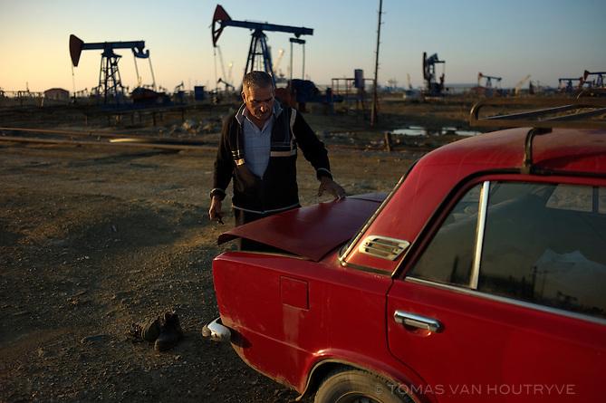 A man closes the trunk on his Soviet-era Lada car in the Bibi-heybat oil fields on the outskirts of Baku, Azerbaijan.