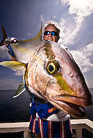 Maldives, Indian Ocean November 2008. Fisherman in his 50s holding an Amberjack (Seriola rivoliana), a member of the carangide family found in all temperate waters.
