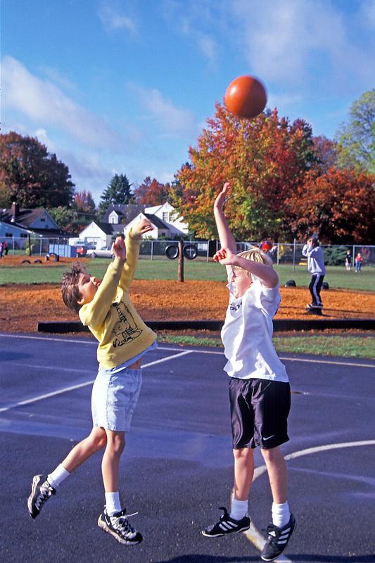 Fifth grade boys playing basketball on playground. Oregon.