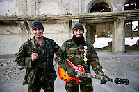 ANA (Afghan National Army) soldiers pose with a guitar of rock band Kabul Dreams in the ruins of a castle in Kabul.