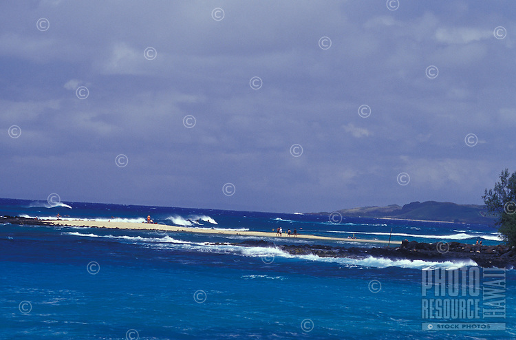 People on sandspit surrounded by blue Pacific Ocean at Poipu Beach, Kauai, Hawaii