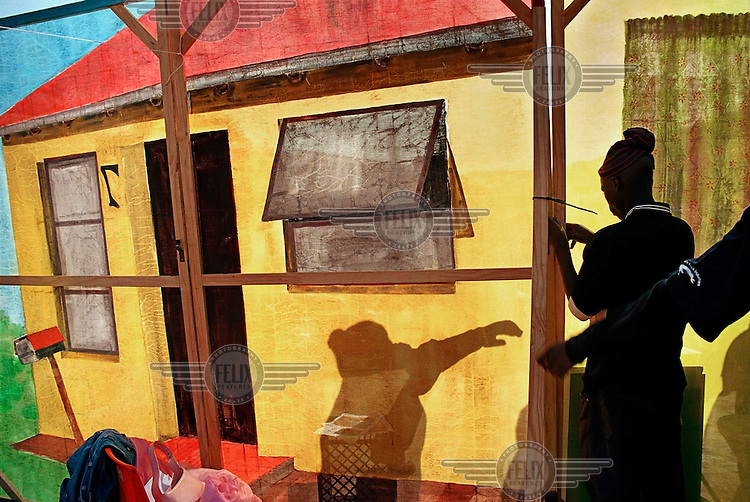 The shadow of a man seen on a mural of a house as a man fixes a frame.