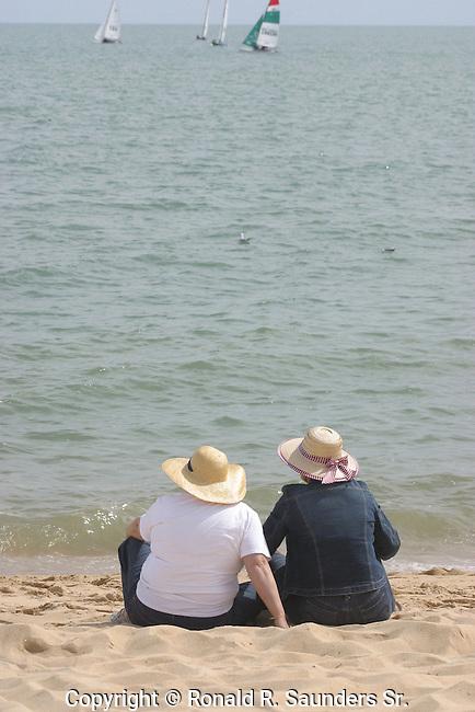TWO WOMEN ON BEACH WATCH REGATTA
