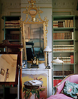 A corner of the bedroom is lined with painted bookshelves and furnished with a hot pink 18th-century Piedmontese walnut dormeuse and antique gilt pier mirror