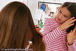 11 year old girl looking at self in mirror self care brushing hair horizontal