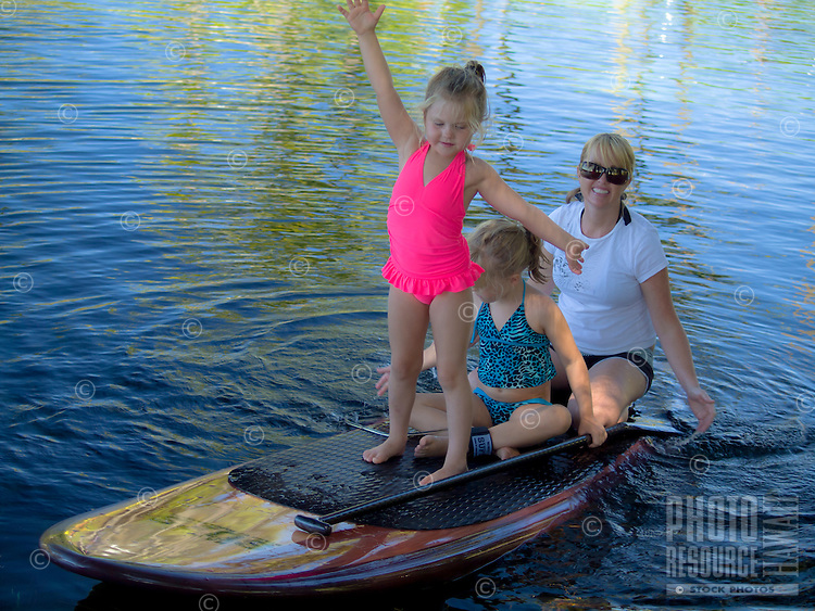 A mom and her two girls float on a standup paddleboard during a beautiful day at Richardson's Ocean Park, Hilo, Big Island.