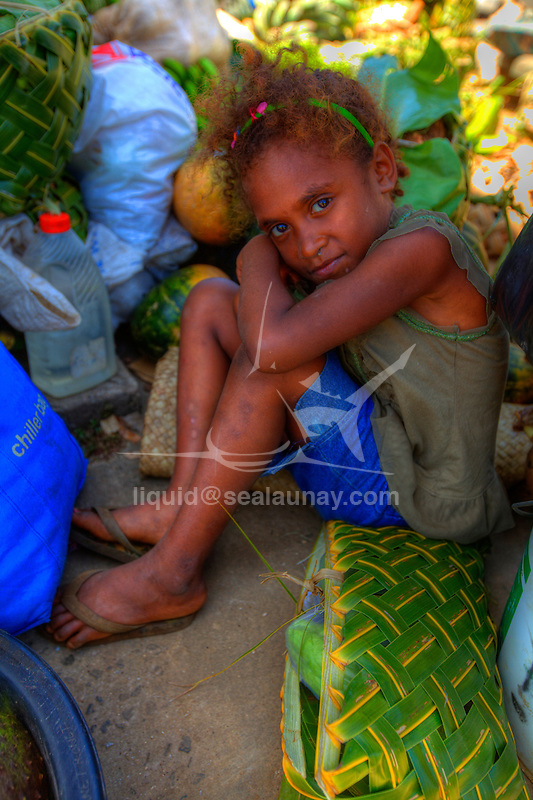 Child at the local market, Port Vila, Vanuatu..Port Vila is the capital and largest city of Vanuatu. Situated on the south coast of the island of Efate, in Shefa Province.Port Vila is the economic and commercial centre of Vanuatu .The population is around 38,000; predominately Melanesian, with small Polynesian, Asian, Australian and European populations, namely French and British..Bislama is spoken by everyone as the day-to-day language. In addition, English and French are also widespread. Other Indigenous languages are also spoken in the city.