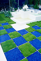Checkerboard pattern squares of moss and blue crushed glass mulch for alternative to lawn grass landscaping, raised modernistic waterfall feature, irises flowers