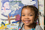 Education Preschool 4-5 year olds portrait of girl with art work behind her closeup