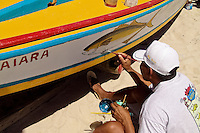 A Brazilian fisherman (jangadeiro) paints a fish picture on his boat on the beach of Prainha, Ceará state, northeastern Brazil, 9 March 2004. Jangadeiros, working on a unique wooden raft boat called jangada, keep the tradition of artisan fishing for more than four hundred years. However, being a fisherman on jangada is highly dangerous job. Jangadeiros spend up to several days on high-sea, sailing tens of kilometres far from the coast, with no navigation on board. In the last two decades jangadeiros have been facing up the pressure from motorized vessels which use modern, effective (and environmentally destructive) fishing methods. Every time jangadeiros come back from the sea with less fish.