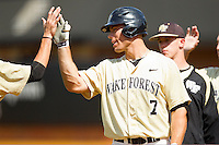 Mac Williamson #7 of the Wake Forest Demon Deacons high fives a teammate after he scored a run against the Georgia Tech Yellow Jackets at Wake Forest Baseball Park on April 15, 2012 in Winston-Salem, North Carolina.  The Demon Deacons defeated the Yellow Jackets 11-3.  (Brian Westerholt/Four Seam Images)