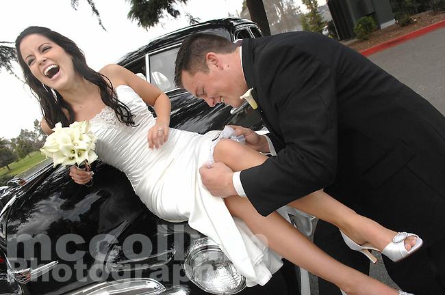 Danielle enjoys her soon to be husband  Ian placing her garter belt on her leg, before their wedding in Manteca, CA