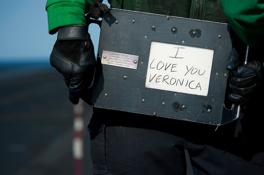120215-N-DR144-115 ARABIAN SEA (Feb. 15, 2012) Aviation Boatswain's Mate (Equipment) Airman Brad Thomas displays a grease pencil Valentine's Day message to his girlfriend on back of an aircraft weight board before launching aircraft from the bow catapults on the flight deck of the Nimitz-class aircraft carrier USS Carl Vinson (CVN 70). Carl Vinson and Carrier Air Wing (CVW) 17 are deployed to the U.S. 5th Fleet area of responsibility.  (U.S. Navy photo by Mass Communication Specialist 2nd Class James R. Evans/Released).