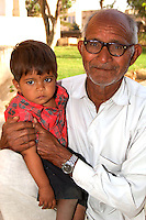 Portrait of Father and boy waiting to be seen outside the medical clinic at Fort Dundlod, India.