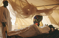 Sudan. West Darfur. Habilah. The non-governmental organization (ngo) Médecins sans Frontières (MSF) Switzerland runs a clinic. A sick old man lies in bed under a mosquito net. © 2004 Didier Ruef