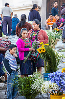 Chichicastenango, Guatemala.  Quiche (Kiche, K'iche') Women Buying Flowers on Steps of Santo Thomas Church on Sunday Morning.