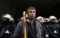 Pictured: A farmer with a stick stands in front of riot police officers  Friday 12 February 2016<br /> Re: Violent clashes between farmers and riot police outside the Ministry of Agricultural Development in Athens, Greece. The farmers travelled from Crete to protest against pension and welfrae reforms proposed by the Greek government,