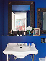 Artwork in the hallway is reflected in the mirror of this deep blue bathroom