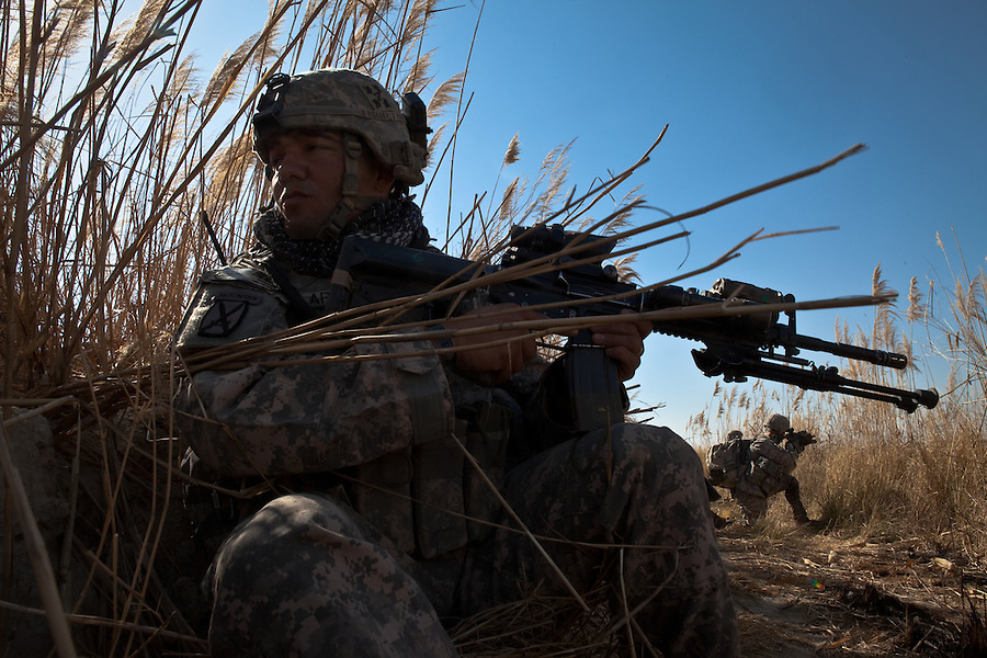 Staff Sgt. Israel Casillas-Arroyo with Charlie Co. 1st Battalion 12th Infantry Regiment, 4th Infantry Division watches near-by farmers working in a field during a patrol in Zhari District, Kandahar, Afghanistan. The violently contested district sits astride the strategically Highway 1 ringroad between Kandahar and Lashkar Gah and is seen by some as the birthplace of the Taliban movement.