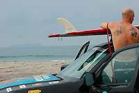 """Isla Los Coronados, Mexico are visible to the South as Tom Jones secures his 14ft paddle board to a vehicle before leaving the US Mexico border at Border Field State Park, the south-western most corner of the contiguous United States, Friday, November 9, 2007.  Jones became the first person to paddle the entire 1250-mile coast of the California on a paddleboard when his three and a half month long journey ended at the border fence in southern San Diego.   The expedition, called """"California Paddle 2007"""" was designed to draw attention to the problem of plastic pollution in the world's oceans and its detrimental effect on marine life.  (Photo Ronan Gray)"""