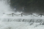 Rain and high waves cover sight seekers at Fort Point under the Golden Gate Bridge in San Francisco.