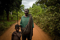 "Enosa Mawa, a congolese refugee on the road between Naandi and Nzara, South Sudan. He fled LRA attacks in Congo and now travels with a spear to protect his family. In the area round yambio villagers have organized ""arrow boys"" a  sort of community watch to guard against  possible LRA attacks.."