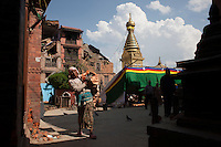 A Nepali woman retrieves her belongings from her destroyed house, in front of the Shoyembho temple, just outside Kathmandu, Nepal