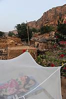 MALI Dogon Land , Dogon village with clay architecture at the Falaise which is UNESCO world heritage, tourist sleeping under mosquito net outdoor in auberge  / MALI, etwa 20 km südoestlich von Bandiagara verlaeuft die rund 200 km lange  Falaise , UNESCO Welterbe, eine teilweise stark erodierte Sandsteinwand bis zu 300 m Hoehe  , hier befinden sich viele Dogon Doerfer in Lehmbau Architektur